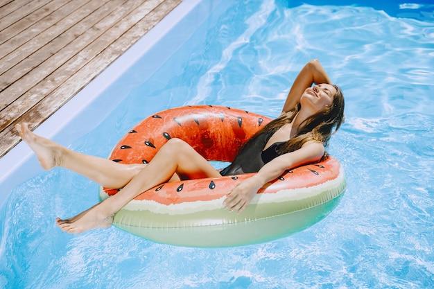 Menina em uma piscina. mulher em um maiô elegante. senhora em férias de verão Foto gratuita