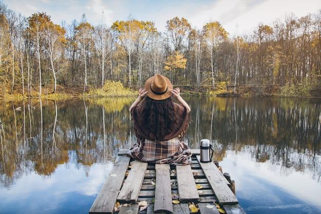 Menina em uma ponte velha de madeira em um lago Foto Premium