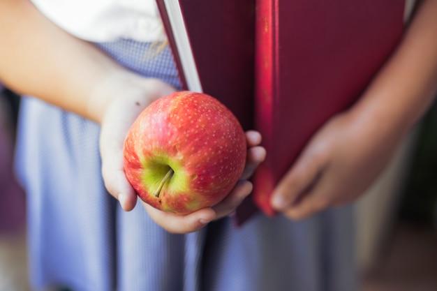 Menina, em, uniforme, com, maçã, e, livros, em, mãos Foto gratuita