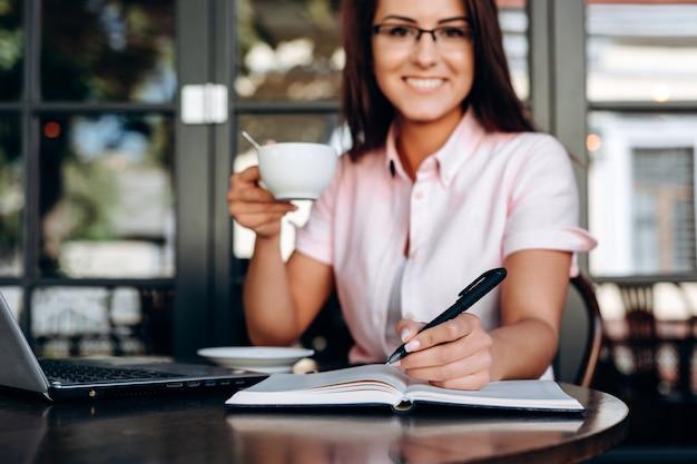 Menina encantadora e sorridente, escrevendo em um caderno, close-up vista Foto Premium