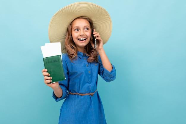 Menina encantadora mostra um passaporte com bilhetes, fala ao telefone e se alegra Foto Premium