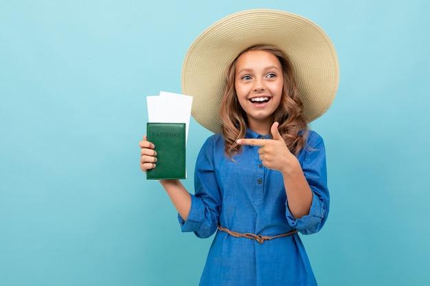Menina encantadora mostra um passaporte com ingressos e se alegra Foto Premium