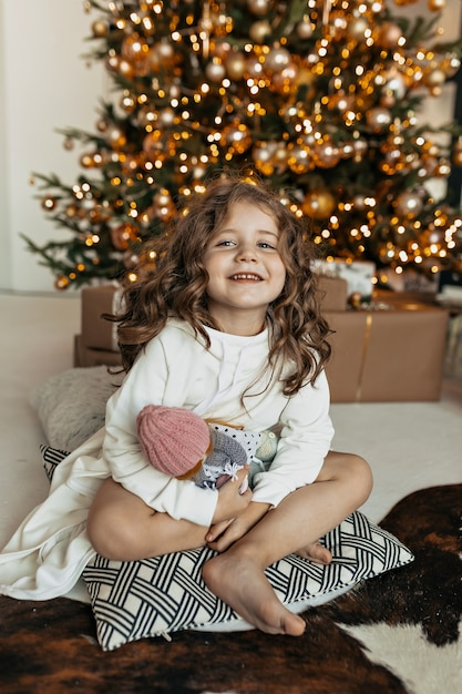 Menina encantadora sentada no travesseiro com o brinquedo na árvore de natal, clima de ano novo, festa de natal Foto gratuita