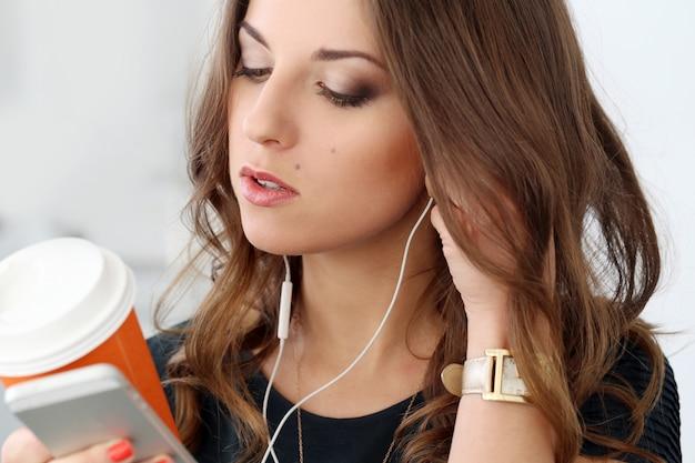 Menina encaracolada com telefone móvel Foto gratuita