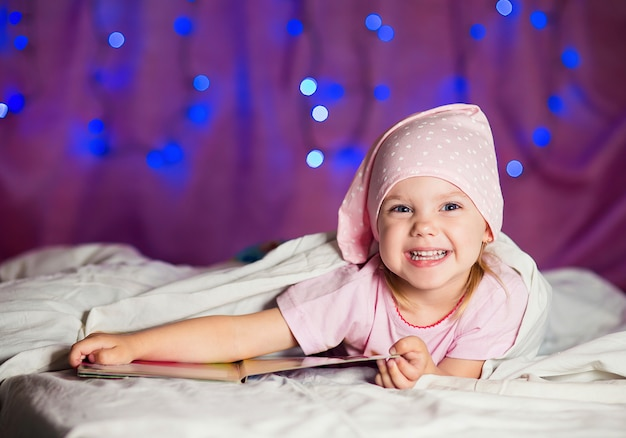 Menina encontra-se na cama em uma bebida com um livro infantil e sorrisos Foto Premium