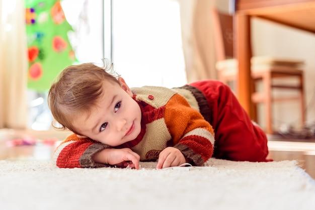 Menina engraçada e bonita sorri para os pais enquanto ela rola no chão em casa .. Foto Premium