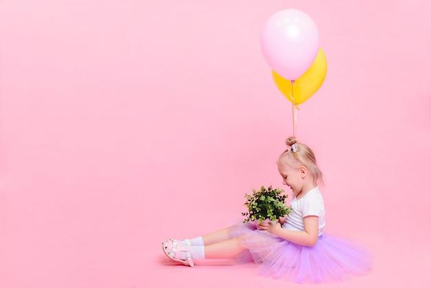 Menina engraçada na camiseta branca e saia lilás com balões em fundo rosa. retrato infantil com espaço para texto. Foto Premium