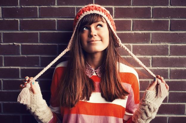 Menina engraçada que joga com seu chapéu Foto gratuita