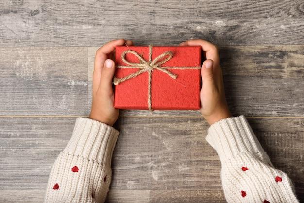 Menina entrega caixa de presente da terra arrendada Foto gratuita