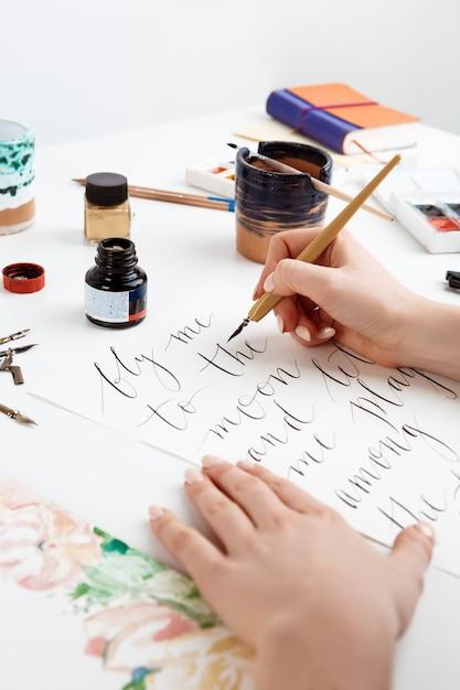 Menina escrevendo caligrafia em cartões postais. design de arte. Foto gratuita