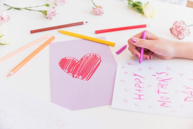 Menina escrevendo feliz dia das mães na folha de papel Foto gratuita