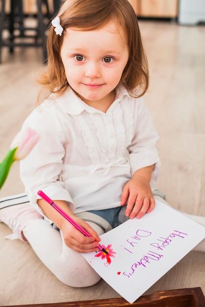 Menina escrevendo feliz dia das mães no papel Foto gratuita
