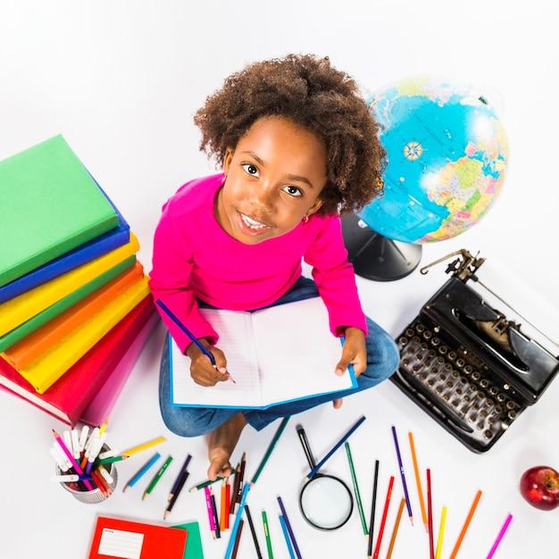 Menina, escrita, em, caderno, em, estúdio Foto gratuita