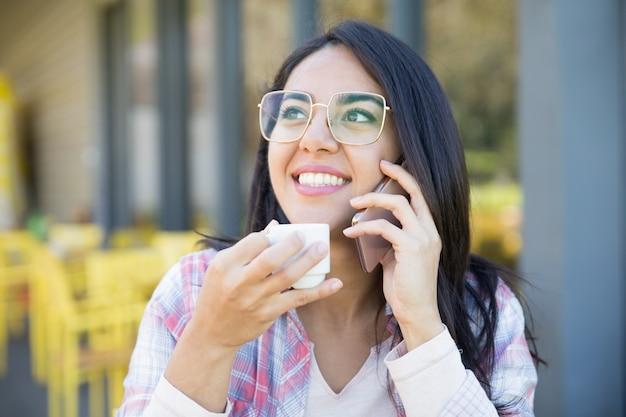 Menina esperta positiva do estudante que aprecia a conversa agradável do telefone Foto gratuita