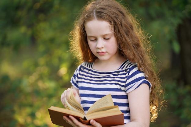Menina esperta que lê o livro ao ar livre. Foto Premium