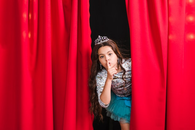 Menina espiando da cortina vermelha fazendo gesto silencioso Foto gratuita