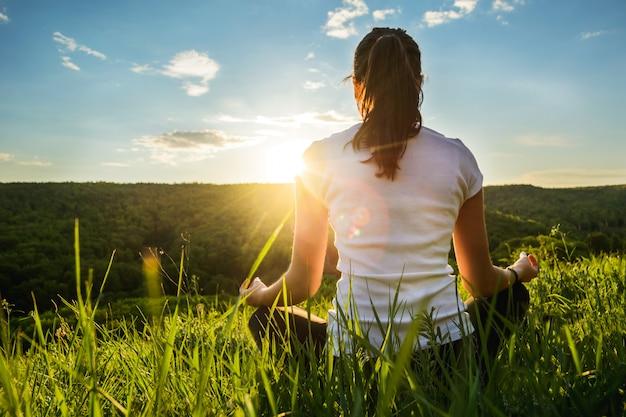 Menina está envolvida em meditação sobre a natureza Foto Premium