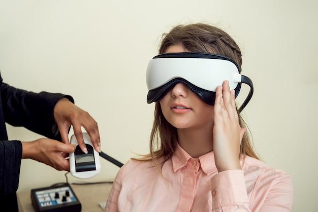 Menina está preocupada com a visão dela. mulher europeia moderna relaxada, sentado no escritório do oftalmologista, esperando quando o procedimento será concluído, usando o rastreador de visão digital durante o check-up Foto gratuita