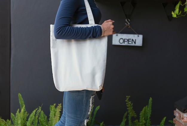Menina está segurando o saco em branco Foto Premium
