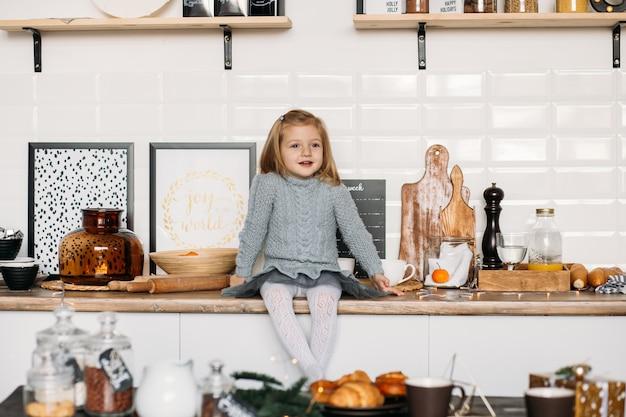 Menina está sentada na mesa da cozinha Foto Premium