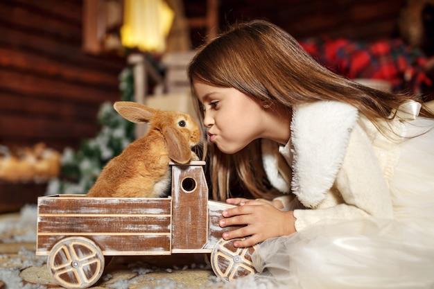 Menina esticar para beijar um coelho sentado em um carro de brinquedo. decoração de natal. conceito de férias Foto Premium
