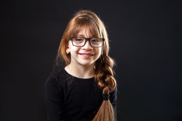 Menina, estudante em copos com pigtail sorrindo no estúdio em um fundo preto Foto Premium