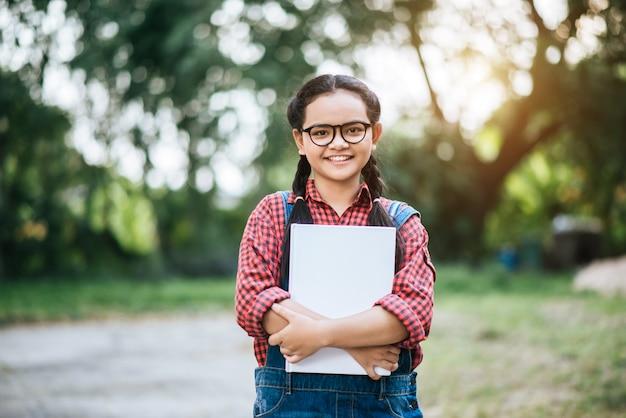 Menina estudante mão abraço livro Foto gratuita
