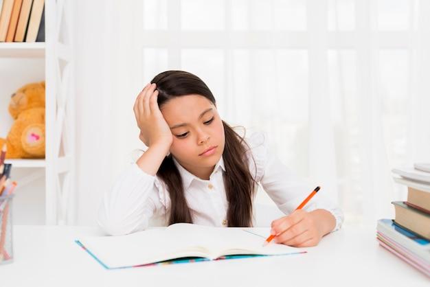 Menina étnica estudando em casa Foto gratuita