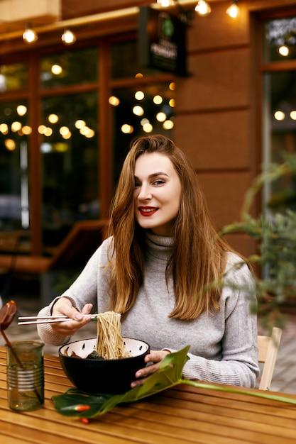 Menina européia nova que come ramen Foto Premium