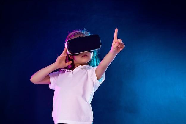 Menina experimentando jogo de fone de ouvido vr. criança, apontando o dedo enquanto estiver usando um dispositivo de jogos para realidade virtual. Foto Premium