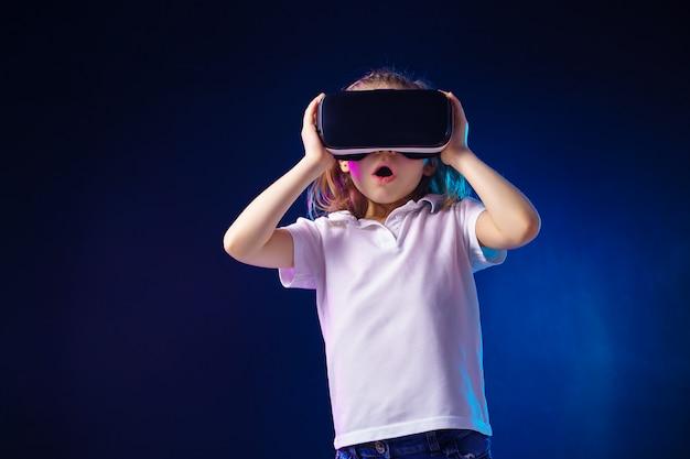 Menina experimentando jogo de fone de ouvido vr. emoções surpreendidas em seu rosto. criança usando um dispositivo de jogos para realidade virtual. Foto Premium