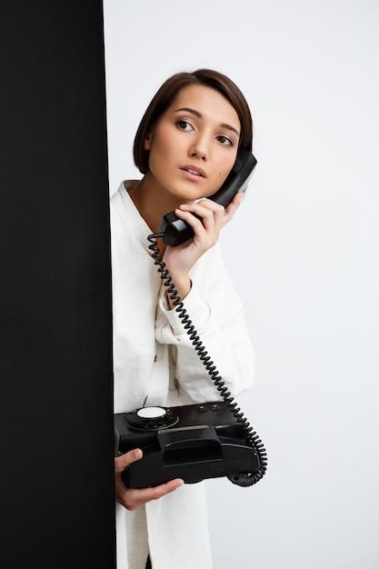 Menina falando no telefone antigo sobre parede preto e branco Foto gratuita