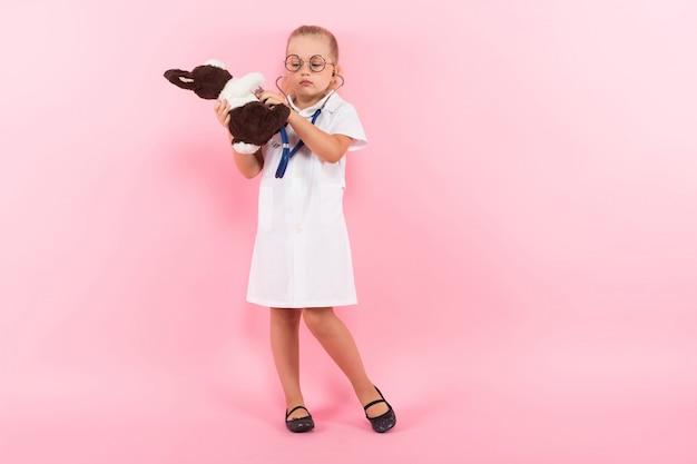 Menina fantasiada de médico com brinquedo Foto Premium