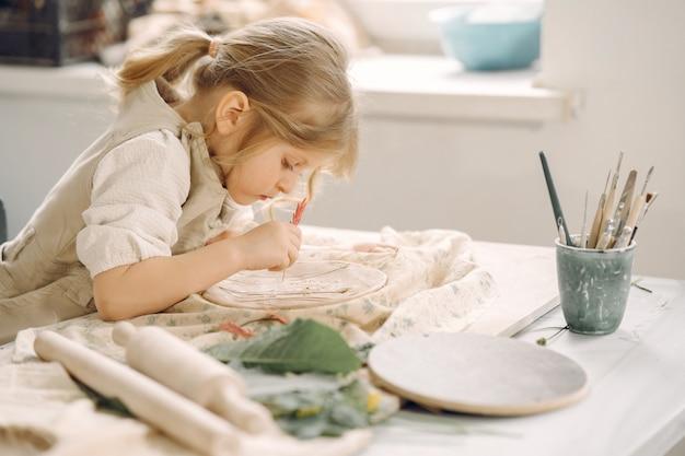 Menina faz um prato de barro e decora Foto gratuita