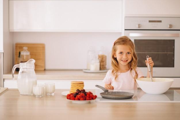 Menina fazendo panquecas na cozinha Foto gratuita