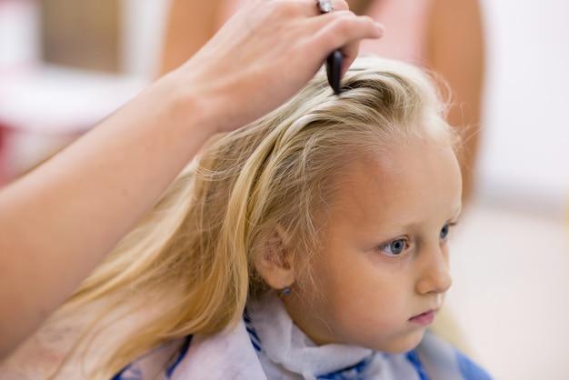 Menina fazendo um corte de cabelo no salão. Foto Premium