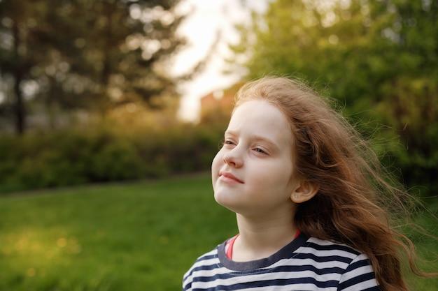 Menina fechou os olhos e respirando com ar fresco soprando. Foto Premium