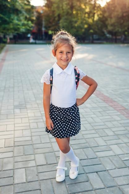 Menina feliz aluno usando mochila e uniforme escolar. garoto olhando para câmera em pé ao ar livre da escola primária. Foto Premium