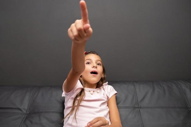 Menina feliz assistindo tv no meio da noite, sentado num sofá na sala de estar em casa Foto Premium