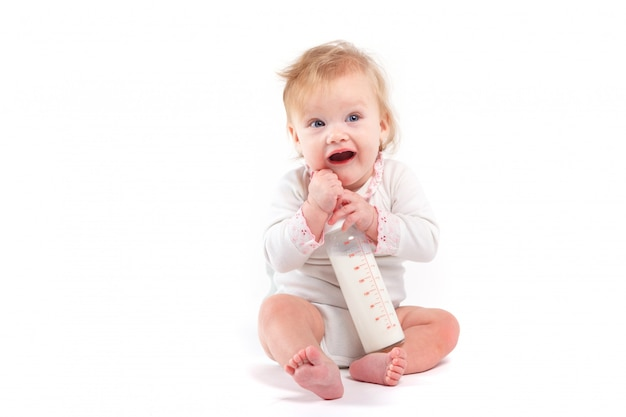 Menina feliz bonitinha na camisa branca com leite Foto Premium