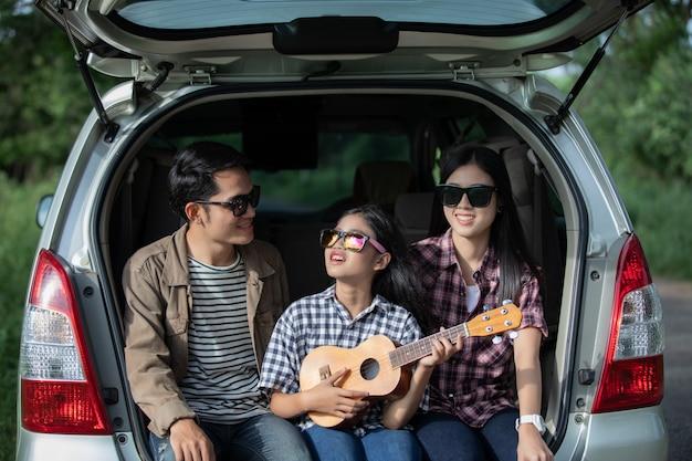 Menina feliz com a família asiática sentada no carro Foto Premium