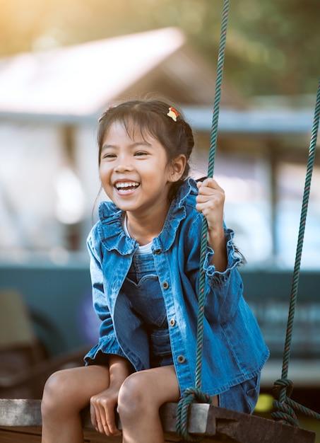 Menina feliz criança asiática se divertindo para jogar em balanços de madeira no parque infantil no parque Foto Premium