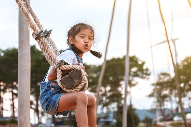Menina feliz criança asiática se divertindo para jogar em balanços de madeira no playground com bela natureza Foto Premium