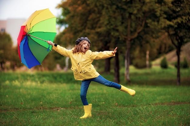 Menina feliz criança engraçada com guarda-chuva em botas de borracha Foto Premium