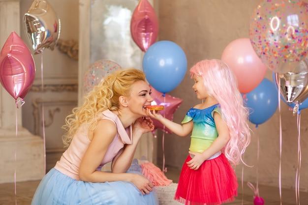 Menina feliz de 3-4 anos em uma peruca rosa alimenta uma rosquinha saborosa para sua mãe, aniversário do bebê Foto Premium