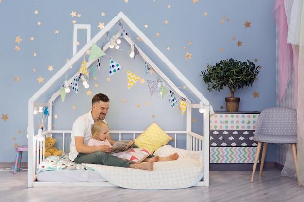 Menina feliz de 3 anos e seu pai bonito, lendo um livro enquanto está sentado na cama de casa bonita Foto Premium
