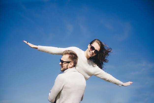 Menina feliz e cara correndo e abraçando em voo contra o céu, viajar conceito de história de amor, foco seletivo Foto Premium