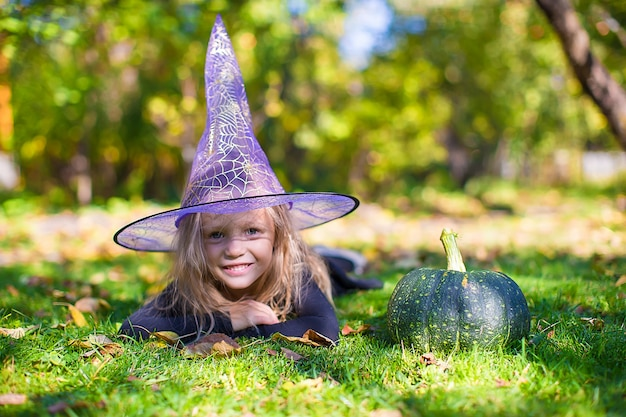 Menina feliz em traje de halloween com jack pumpkin.trick ou deleite Foto Premium