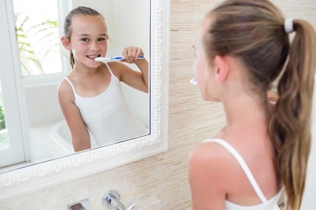 Menina feliz, escovar os dentes no banheiro Foto Premium