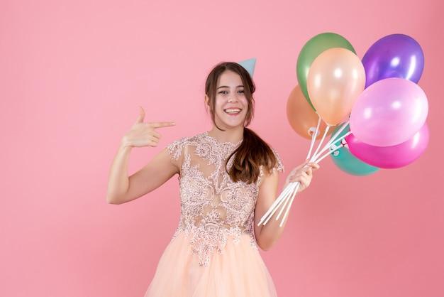 Menina feliz festeira com boné segurando balões apontando com o dedo ela mesma no rosa Foto gratuita